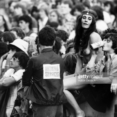 A roadie chats with one of the young fans leaning against a barrier at the annual Knebworth Rock Festival. (Photo by © Hulton-Deutsch Collection/CORBIS/Corbis via Getty Images)